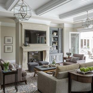 サンフランシスコの中サイズのトラディショナルスタイルのおしゃれなファミリールーム (ベージュの壁、濃色無垢フローリング、標準型暖炉、石材の暖炉まわり、壁掛け型テレビ、茶色い床) の写真