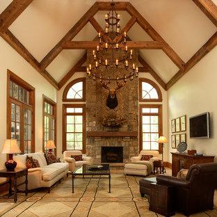 Cette photo montre une salle de séjour montagne fermée avec un mur beige, un sol en travertin, une cheminée standard, un manteau de cheminée en pierre, un téléviseur fixé au mur et un sol beige.