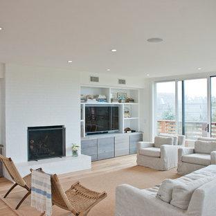 ニューヨークのコンテンポラリースタイルのおしゃれなオープンリビング (白い壁、無垢フローリング、標準型暖炉、レンガの暖炉まわり、壁掛け型テレビ) の写真