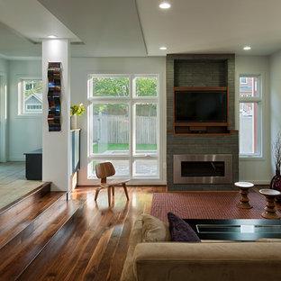 ワシントンD.C.のコンテンポラリースタイルのおしゃれなオープンリビング (横長型暖炉、壁掛け型テレビ、マルチカラーの壁、無垢フローリング、石材の暖炉まわり、茶色い床) の写真