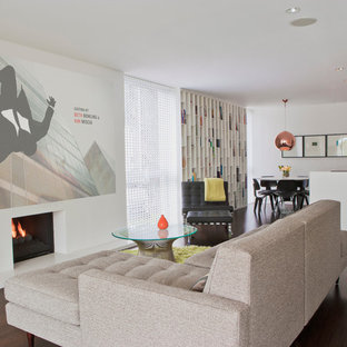 Example of a 1960s open concept dark wood floor family room design in Orange County with white walls and a standard fireplace