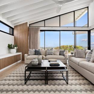 シドニーの大きいビーチスタイルのおしゃれなファミリールーム (白い壁、淡色無垢フローリング、据え置き型テレビ、ベージュの床) の写真