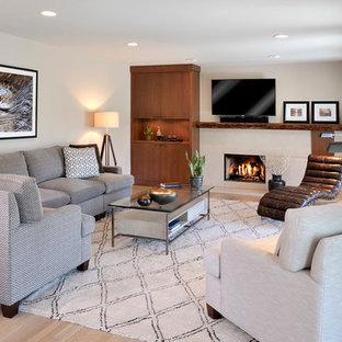ニューヨークのコンテンポラリースタイルのおしゃれなファミリールーム (ベージュの壁、淡色無垢フローリング、標準型暖炉、壁掛け型テレビ、コンクリートの暖炉まわり) の写真