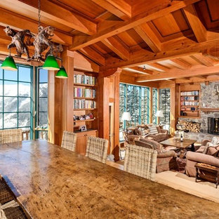 Huge mountain style open concept brown floor and light wood floor family room photo in Denver with a standard fireplace, brown walls, a stone fireplace and no tv