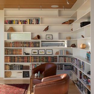 Cette image montre une petite salle de séjour avec une bibliothèque ou un coin lecture vintage avec un mur blanc, un sol en bois clair et un sol marron.