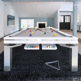 Aménagement d'une grand salle de séjour moderne ouverte avec salle de jeu, un mur bleu, un sol en bois clair, une cheminée standard, un manteau de cheminée en métal et un téléviseur fixé au mur.