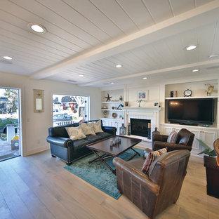 Modelo de sala de estar abierta, campestre, grande, con paredes blancas, suelo de madera clara, chimenea tradicional, marco de chimenea de ladrillo, televisor independiente y suelo marrón