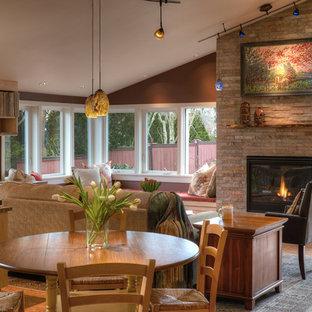 Immagine di un soggiorno stile americano di medie dimensioni e aperto con pareti rosse, pavimento in sughero, camino classico, cornice del camino in mattoni, libreria, nessuna TV e pavimento marrone