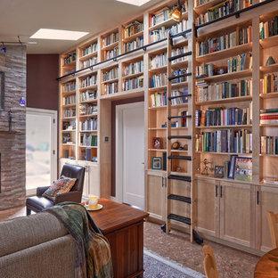 Immagine di un soggiorno american style di medie dimensioni e aperto con libreria, pareti rosse, pavimento in sughero, camino classico, cornice del camino in pietra, nessuna TV e pavimento marrone