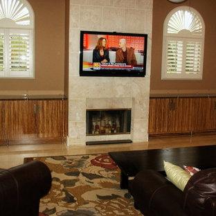Modelo de sala de estar con biblioteca abierta, de estilo zen, de tamaño medio, con suelo de travertino, chimenea tradicional, marco de chimenea de piedra, televisor colgado en la pared y paredes marrones
