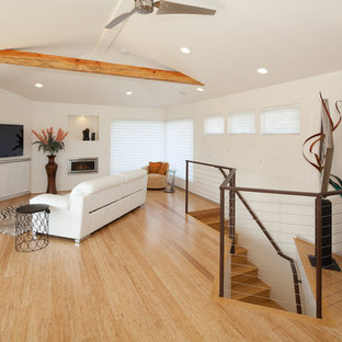 Example of a trendy loft-style light wood floor and beige floor family room design in San Luis Obispo with white walls, a wall-mounted tv and a standard fireplace