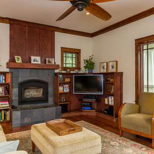 Arts and crafts dark wood floor family room photo in Other with beige walls, a standard fireplace, a stone fireplace and a corner tv
