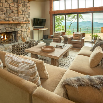 Large mountain style open concept medium tone wood floor and brown floor family room photo in Charlotte with beige walls, a standard fireplace, a stone fireplace and a wall-mounted tv