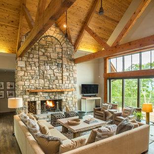 Modelo de sala de estar abierta, rústica, grande, con paredes beige, chimenea tradicional, marco de chimenea de piedra, televisor colgado en la pared, suelo marrón y suelo de madera en tonos medios