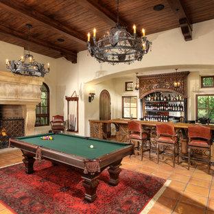 Esempio di un soggiorno mediterraneo con angolo bar, pareti beige, pavimento in terracotta, camino classico e TV a parete