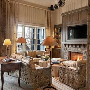 Imagen de sala de estar cerrada, de estilo de casa de campo, de tamaño medio, con paredes beige, suelo de travertino, chimenea tradicional, marco de chimenea de piedra, pared multimedia y suelo beige