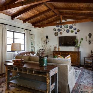 Imagen de sala de estar cerrada, mediterránea, de tamaño medio, sin chimenea, con paredes blancas, televisor colgado en la pared, suelo de baldosas de terracota y suelo rojo