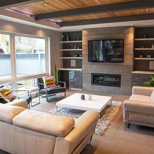 バンクーバーの中サイズのモダンスタイルのおしゃれなファミリールーム (グレーの壁、セラミックタイルの床、横長型暖炉、コンクリートの暖炉まわり、壁掛け型テレビ) の写真