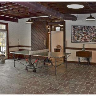 Imagen de sala de juegos en casa tipo loft, de estilo de casa de campo, grande, con paredes blancas, suelo de ladrillo, televisor colgado en la pared y suelo multicolor