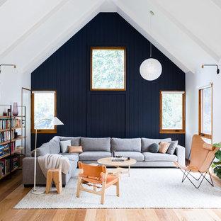 Modelo de sala de estar con biblioteca cerrada, campestre, con paredes multicolor, suelo de madera en tonos medios y suelo marrón