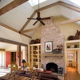 Diseño de sala de estar abierta, campestre, con paredes beige, suelo de madera en tonos medios, chimenea tradicional y marco de chimenea de ladrillo