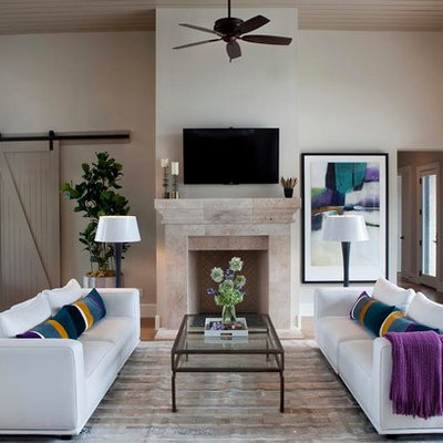 Family room - contemporary open concept medium tone wood floor family room idea in Austin with a standard fireplace, a stone fireplace, a wall-mounted tv and beige walls