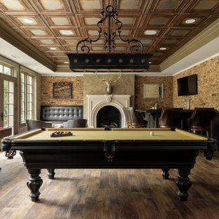Large elegant enclosed medium tone wood floor, brown floor and brick wall game room photo in Richmond with brown walls, a standard fireplace, a plaster fireplace and a wall-mounted tv
