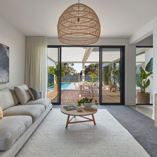 Design ideas for a contemporary family room in Melbourne with white walls, carpet and grey floor.