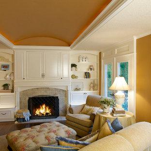 Aménagement d'une salle de séjour classique avec un mur orange, un sol en bois foncé, une cheminée standard et un téléviseur dissimulé.