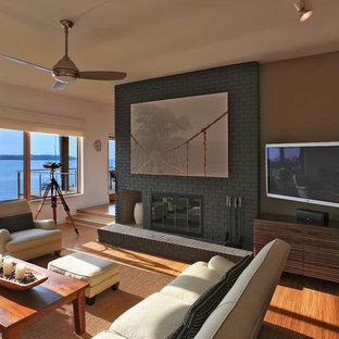 Idee per un soggiorno minimal con pareti beige, pavimento in legno massello medio, camino classico, cornice del camino in mattoni e porta TV ad angolo