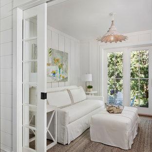 Modelo de sala de estar cerrada, costera, con paredes blancas, suelo de madera clara y suelo marrón