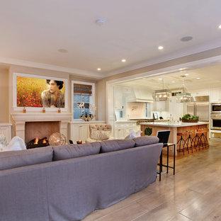 Esempio di un soggiorno stile marinaro aperto con pareti beige, pavimento in legno massello medio, camino classico, cornice del camino in pietra, TV a parete e pavimento beige
