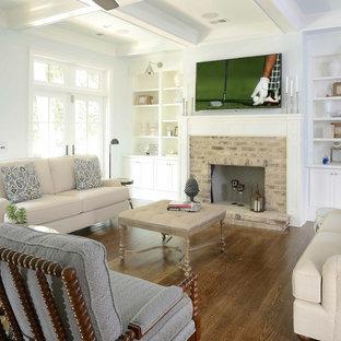 Cette photo montre une salle de séjour bord de mer avec un mur blanc, un sol en bois foncé, un téléviseur fixé au mur, une cheminée standard et un manteau de cheminée en pierre.