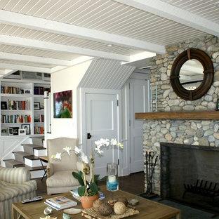 Aménagement d'une salle de séjour bord de mer de taille moyenne et ouverte avec un mur blanc, un sol en bois foncé, une cheminée standard, un manteau de cheminée en pierre, un téléviseur encastré et un sol marron.