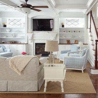 ニューヨークの大きいビーチスタイルのおしゃれなファミリールーム (ベージュの壁、標準型暖炉、タイルの暖炉まわり、壁掛け型テレビ、濃色無垢フローリング) の写真