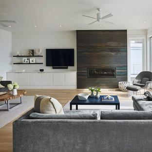 Exemple d'une grande salle de séjour tendance ouverte avec un mur blanc, un sol en bois clair, une cheminée ribbon, un manteau de cheminée en métal, un téléviseur fixé au mur et un sol jaune.