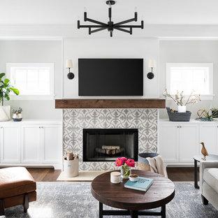 Foto di un soggiorno costiero di medie dimensioni con pareti grigie, camino classico, cornice del camino piastrellata, TV a parete, pavimento marrone e parquet scuro
