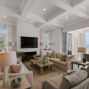 Imagen de sala de estar abierta, marinera, extra grande, con paredes blancas, televisor colgado en la pared, suelo de madera clara, chimenea tradicional y marco de chimenea de baldosas y/o azulejos