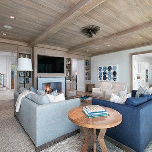 ニューヨークの大きいビーチスタイルのおしゃれな独立型ファミリールーム (ライブラリー、白い壁、淡色無垢フローリング、標準型暖炉、壁掛け型テレビ、石材の暖炉まわり) の写真