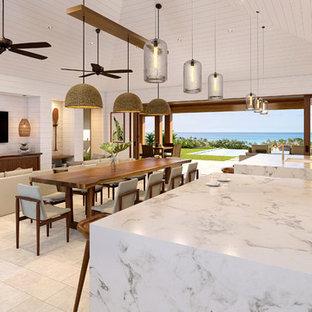 ハワイの大きいビーチスタイルのおしゃれなファミリールーム (ゲームルーム、白い壁、磁器タイルの床、壁掛け型テレビ、ベージュの床) の写真