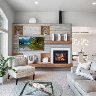 ソルトレイクシティのビーチスタイルのおしゃれなファミリールーム (グレーの壁、カーペット敷き、標準型暖炉、壁掛け型テレビ、グレーの床) の写真