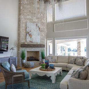 ジャクソンビルのビーチスタイルのおしゃれなファミリールーム (ベージュの壁、無垢フローリング、コーナー設置型暖炉、レンガの暖炉まわり、壁掛け型テレビ、茶色い床) の写真