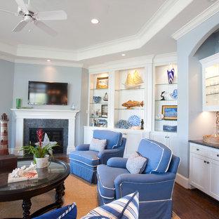 ヒューストンの大きいトラディショナルスタイルのおしゃれなファミリールーム (青い壁、濃色無垢フローリング、壁掛け型テレビ、ホームバー、タイルの暖炉まわり、コーナー設置型暖炉) の写真