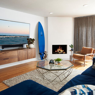 Example of a mid-sized coastal open concept medium tone wood floor and brown floor family room design in Los Angeles with white walls, a ribbon fireplace, a plaster fireplace and a wall-mounted tv