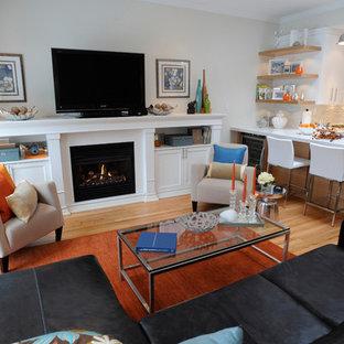 Modelo de sala de estar abierta, costera, de tamaño medio, con suelo de madera en tonos medios, chimenea tradicional, televisor independiente, paredes blancas y suelo beige