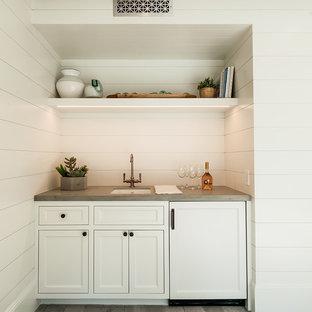 Modelo de sala de estar cerrada, de estilo de casa de campo, con paredes blancas, suelo de piedra caliza, chimenea tradicional, marco de chimenea de hormigón y suelo gris