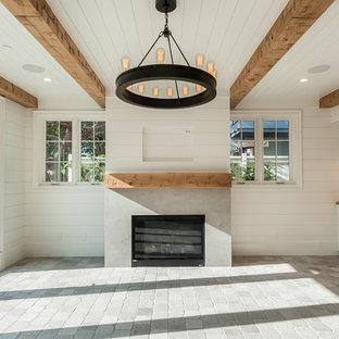 Diseño de sala de estar cerrada, de estilo de casa de campo, con paredes blancas, suelo de piedra caliza, chimenea tradicional, marco de chimenea de hormigón y suelo gris