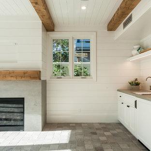 Ejemplo de sala de estar cerrada, de estilo de casa de campo, con paredes blancas, suelo de piedra caliza, chimenea tradicional, marco de chimenea de hormigón y suelo gris