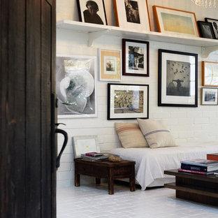 Esempio di un soggiorno industriale di medie dimensioni con pareti bianche, pavimento in mattoni e nessun camino