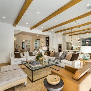 Immagine di un grande soggiorno chic aperto con pareti bianche, camino classico, cornice del camino in metallo, pavimento marrone, parquet chiaro, TV a parete e sala giochi